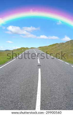 Uphill rural road with a rainbow and blue sky and clouds in the distance. - stock photo