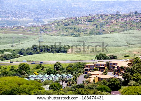 upmarket housing estate with sprawling low cost housing in background bisected by motorway - stock photo