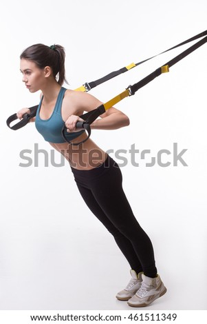 Upper body exercise concept. Image of beautiful woman exercising with suspension straps in studio. Lady posing in full length. TRX concept isolated on white background.