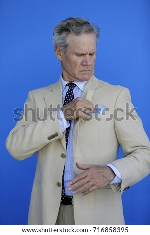 Upper body image of a mature businessman on a blue wall