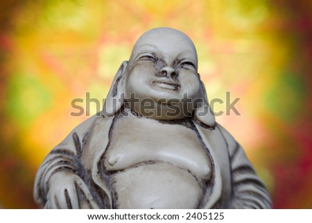 Upper body of a Buddha figurine from asian religion is shown against a glowing eastern style background. - stock photo