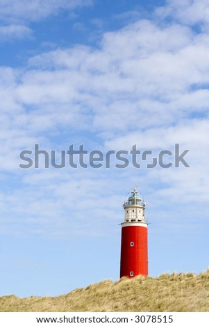 Upper part of a red lighthouse above the dunes.