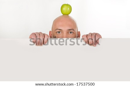 Upper part of bald man�s face with apple on top behind white partition - stock photo