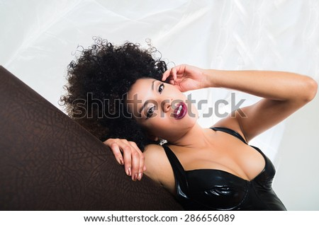 upper part of girl wearing lingerie lying sideways on sofa looking at camera with sexy facial expression