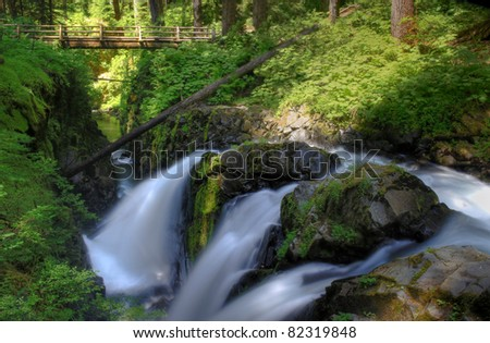 Upper Sol Duc Falls Including Bridge and River Gorge In Olympic Mountains National Park.  Three Distinct Sections Of The Falls Captured At Slow Shutter Speed To Produce Motion Blurred Silky Effect.