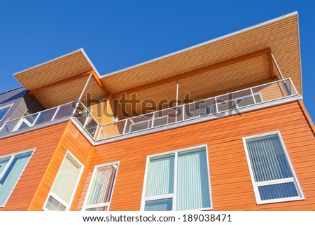 Upper storey detail of timber clad apartment building painted bright with penthouse balcony under blue sky - stock photo
