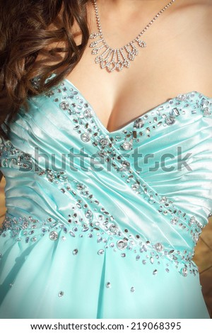 Upper torso of a young caucasian woman in a formal dance dress. She is wearing jewellery and has soft curls on her right - stock photo