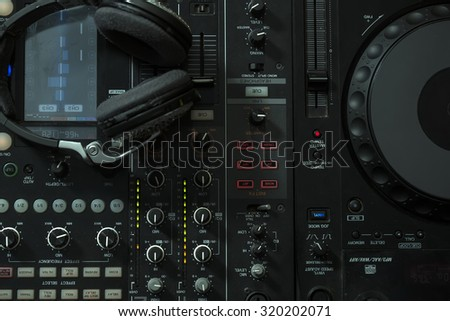 Upper view closeup of dj musical mixer professional console black color with many buttons and knobs and glamour headphones with pastes in night club or studio on digital background, horizontal picture - stock photo