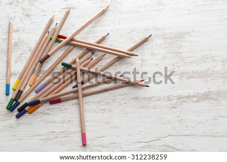 Upper view of a pile of colored pencils on a white wooden table. - stock photo