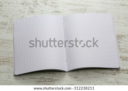 Upper view of an open notebook with squares on a white wooden table. - stock photo