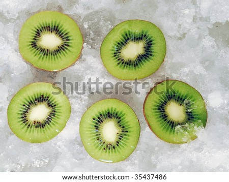 Upper view of five halves fresh fruit on ice cubes. Cut kiwis on ice background