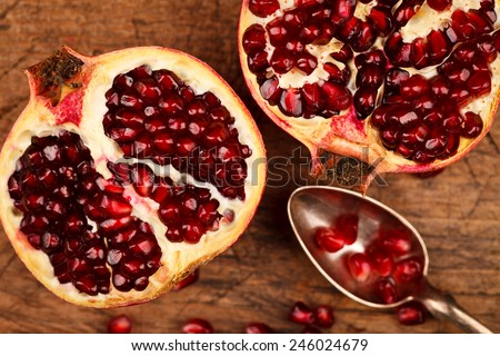 Upper view of grenadine fruits and seeds with silver teaspoon, rustic background - stock photo