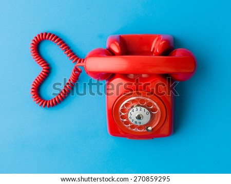 upper view of red phone with heart shape made out of its cable, on blue background - stock photo