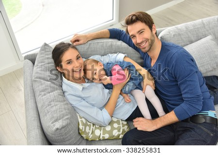 Upper view of young family relaxing in sofa - stock photo