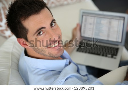 Upper view of young man using laptop computer at home - stock photo