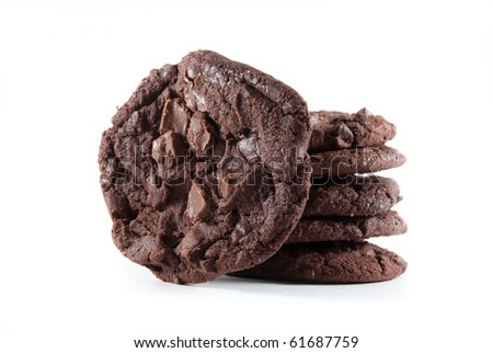 Upright cookie against stack of double chocolate chip cookies on white isolated background. - stock photo