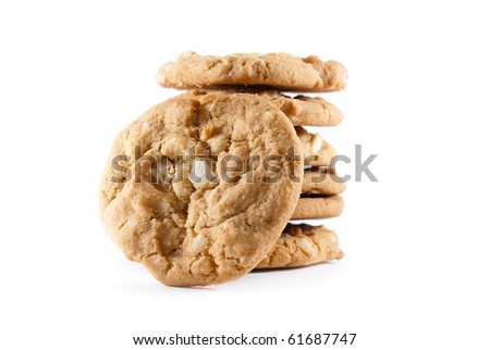 Upright cookies against a stack of macadamia nut cookies on a white isolated background. - stock photo