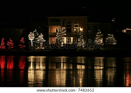 Upscale home with christmas lights reflecting off of lake - stock photo
