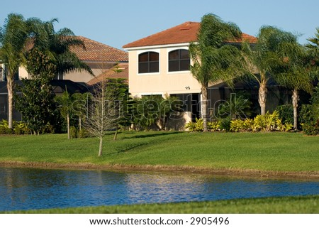 Upscale luxury house in tropical environment near the golf lake - stock photo