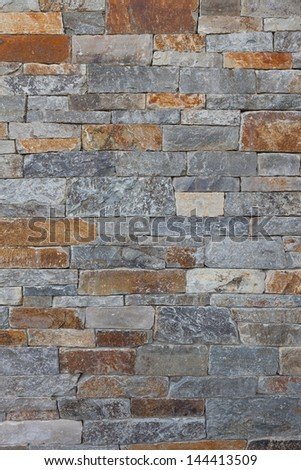Upscale natural stone wall pattern or background, constructed with a high level of craftsmanship. Marble, granite, slate stone material. Gray and some beige, brown stone pieces, slabs or bricks.