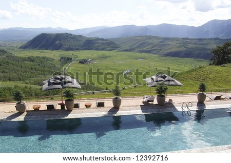 Upscale resort and spa has a pool terrace overlooking the valley and mountains in Wyoming - stock photo