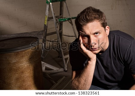 Upset adult male sitting with barrel and ladder - stock photo