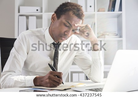 Upset african american businessman working on project at office desk with laptop, notepad and smartphone. Shelf with documents in the background - stock photo