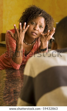 Upset African-American woman talking with a male family member in kitchen setting - stock photo