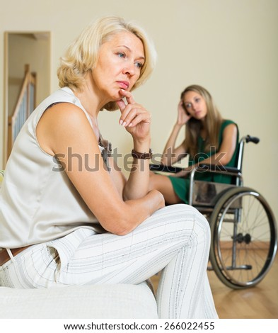 Upset aged woman and handicapped girl having domestic quarrel - stock photo