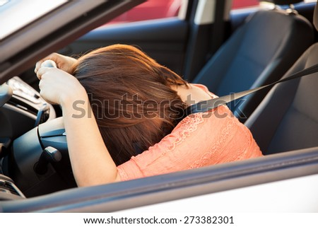 Upset and stressed brunette leaning on the steering wheel of a car - stock photo