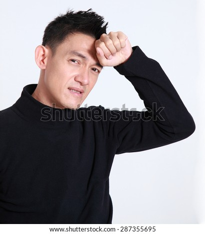 Upset asian man sick standing with his hand holding his for head.