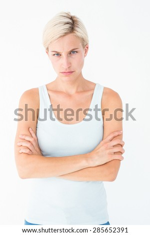 Upset blonde looking at camera with arms crossed on white background