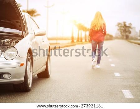 Upset blonde woman leaving her broken roadster - stock photo