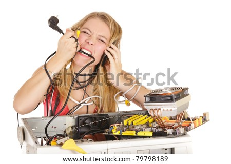 upset bond woman trying to repair computer and biting power cord - stock photo