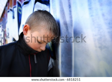 upset boy against a wall - stock photo