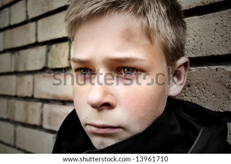 upset boy leaning against a wall