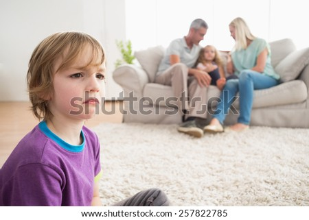 Upset boy sitting on floor while parents enjoying with sister on sofa at home - stock photo