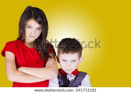 Upset brother and sister looking to camera over yellow background. - stock photo