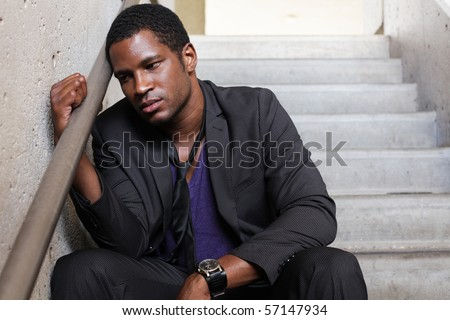 Upset business man sitting in Stairwell - stock photo
