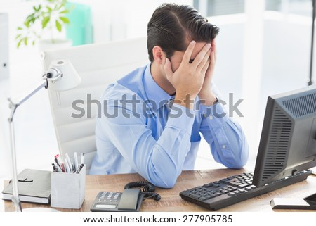 Upset businessman hiding his face in the office - stock photo