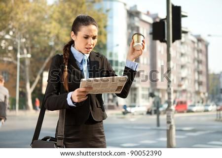 upset businesswoman reading bad news in newspaper, outdoor - stock photo