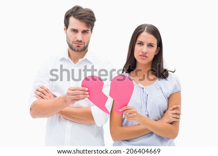 Upset couple holding two halves of broken heart on white background - stock photo