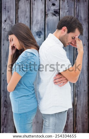 Upset couple not talking to each other after fight against grey wooden planks - stock photo