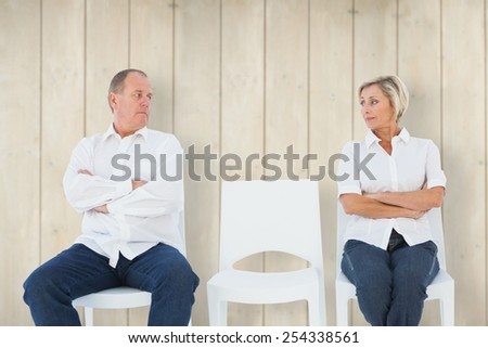 Upset couple not talking to each other after fight against wooden planks - stock photo