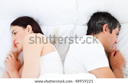 Upset couple sleeping in their bed separately after a row - stock photo