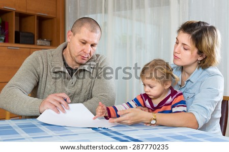 Upset couple with child sitting at the table with financial documents