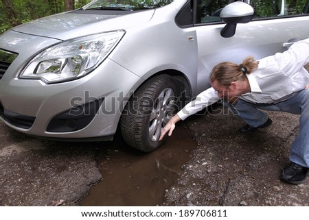 Upset driver man in front of automobile watching damaged car of road full of cracked potholes in pavement - stock photo