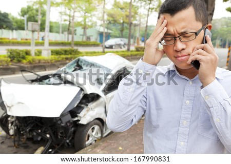 upset driver talking on mobile phone with crash car  - stock photo