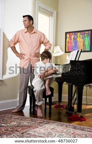 Upset father standing beside teenage son at home - stock photo