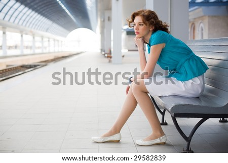 Upset girl in casual clothing on railway station - stock photo